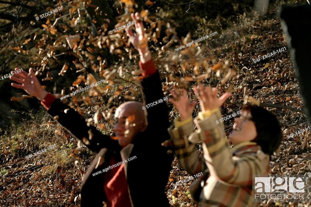 Stock Photo: Man and woman throwing leaves in the air.