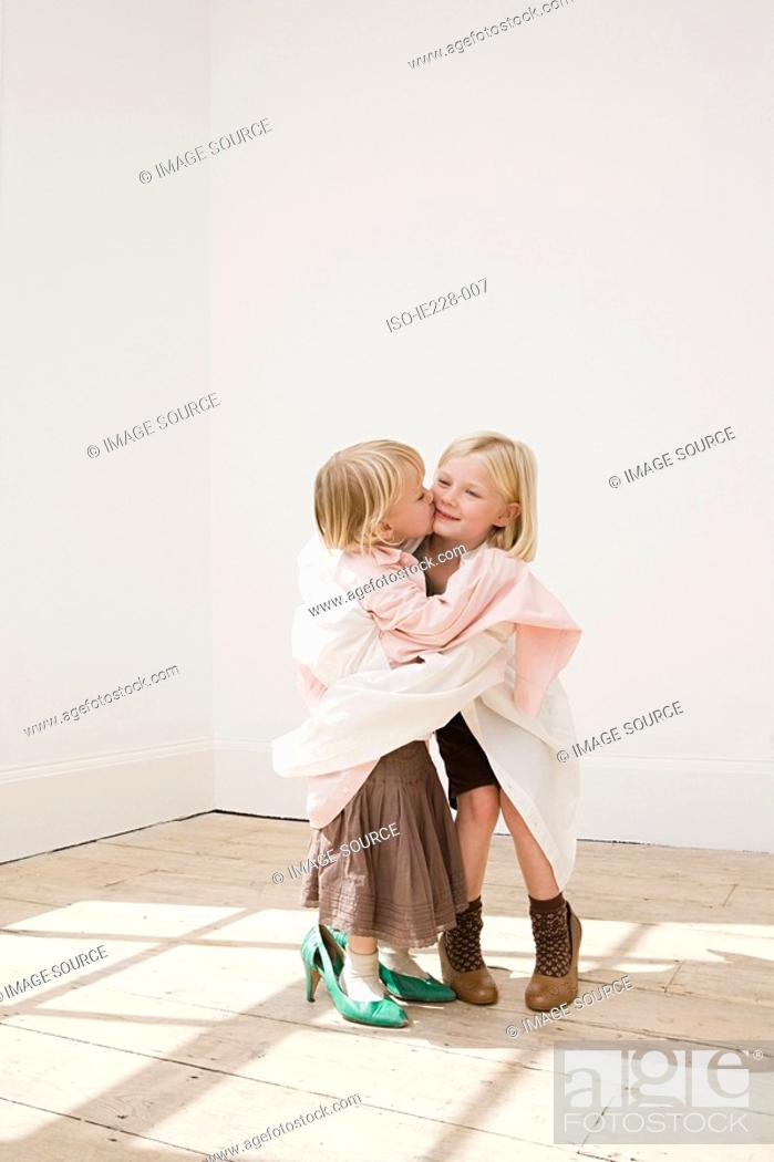Stock Photo: Two young sisters kissing.