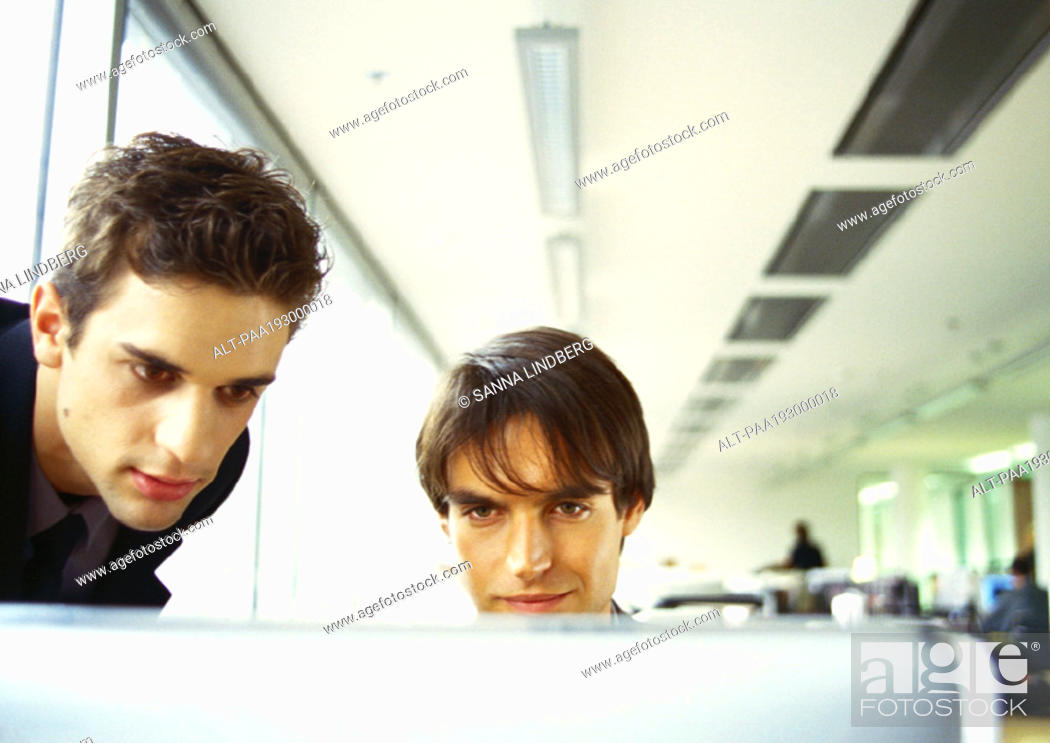 Stock Photo: Two men's heads, edge of computer screen in foreground.