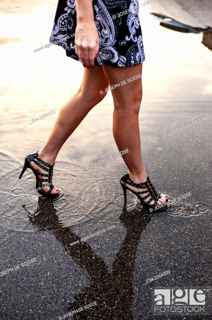 Stock Photo: Partial view of a woman's bare legs walking on the street.