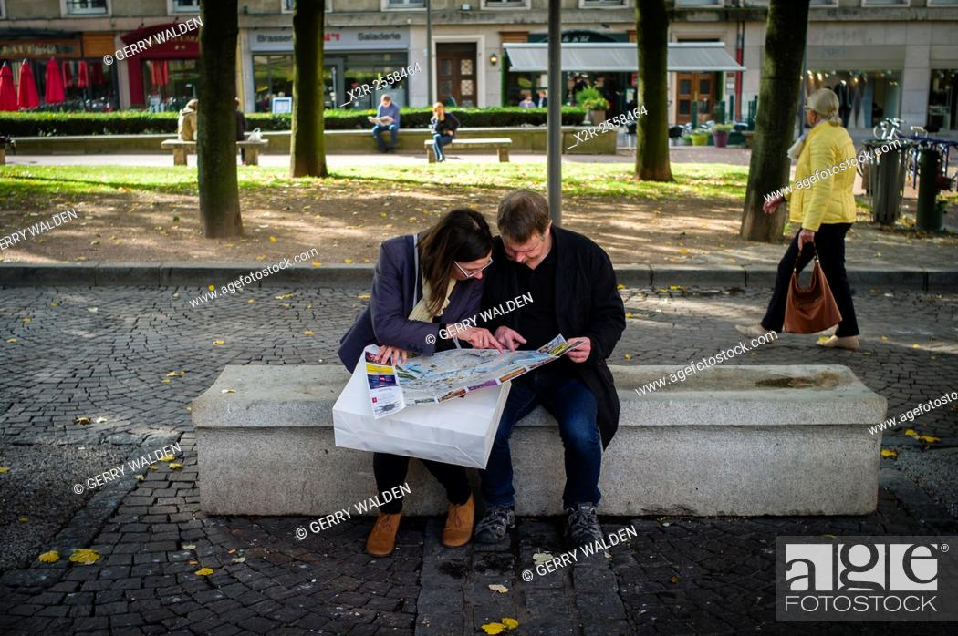 Stock Photo: Two people sit and study a map in the precepts of Rouen Cathedral, Normandy, France.