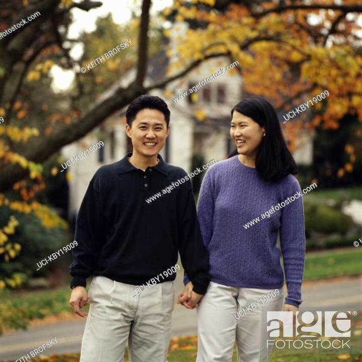 Imagen: Asian couple walking hand in hand.