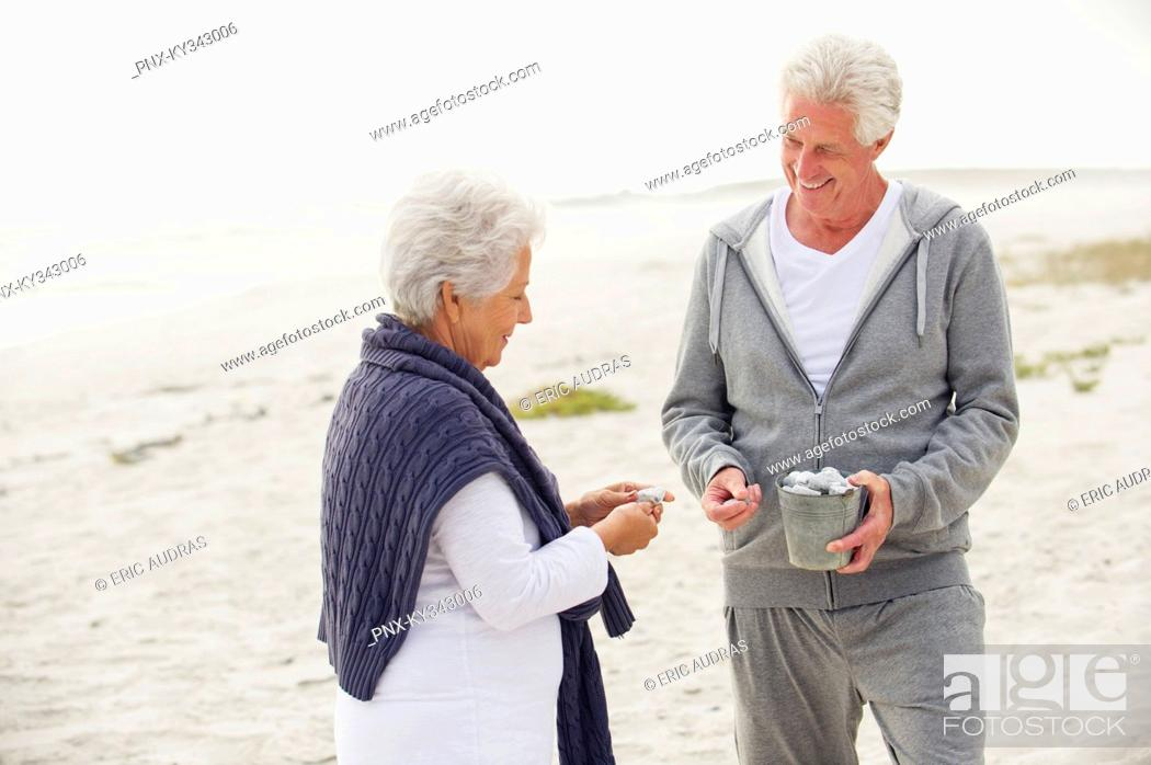 Stock Photo: Senior couple collecting shell on the beach.