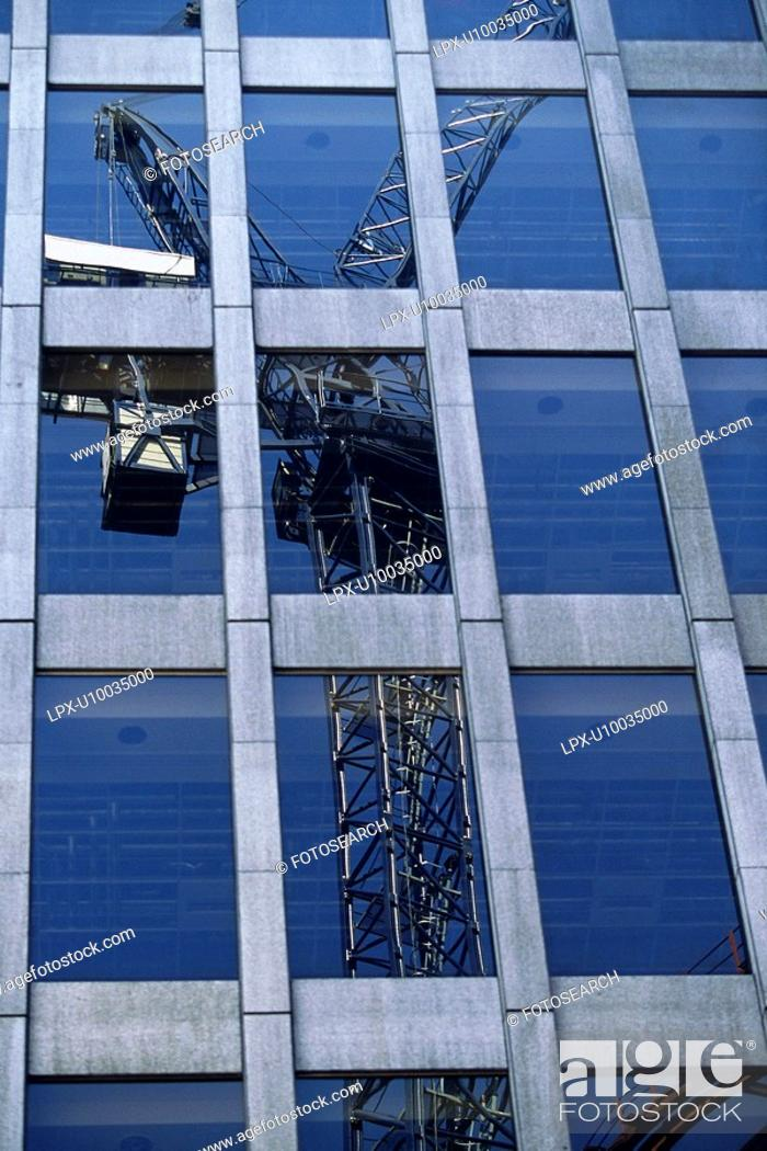 Stock Photo: Tower crane reflected in glass facade of modern high rise building.