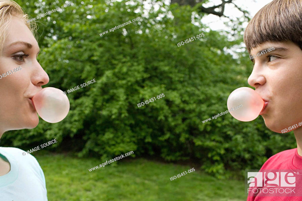 Stock Photo: Teenage couple blowing bubble gum bubbles.