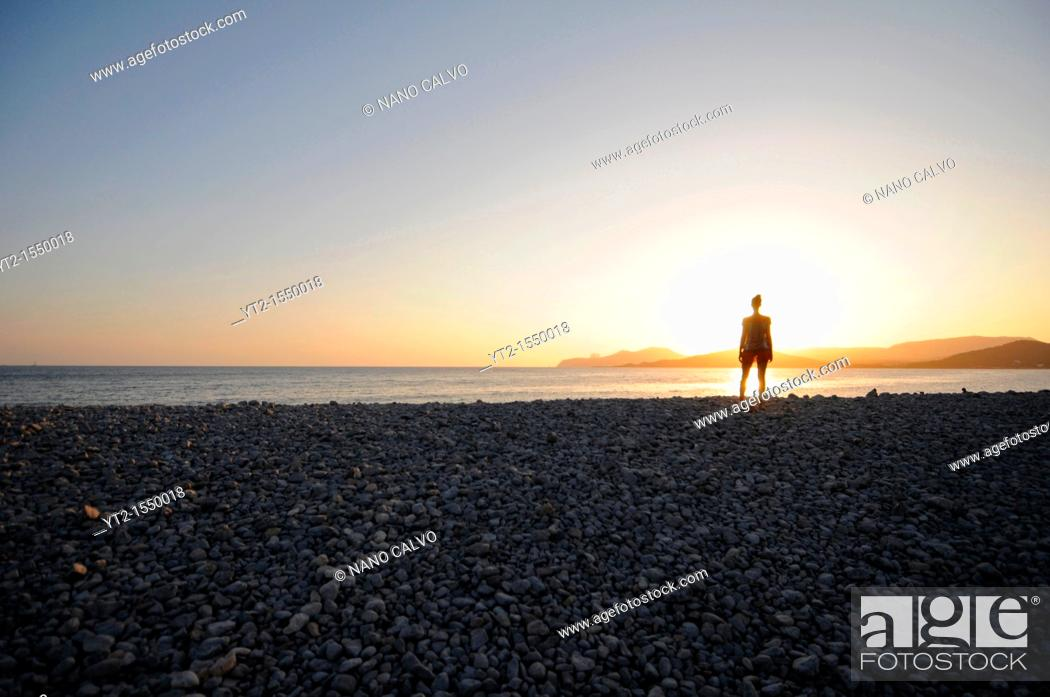 Stock Photo: Silhouette of young woman at sunset.