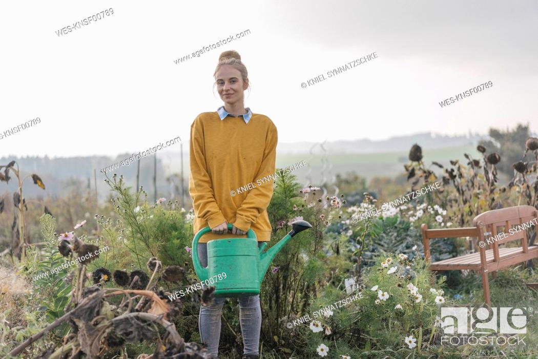 Stock Photo: Smiling young woman holding watering can in cottage garden.
