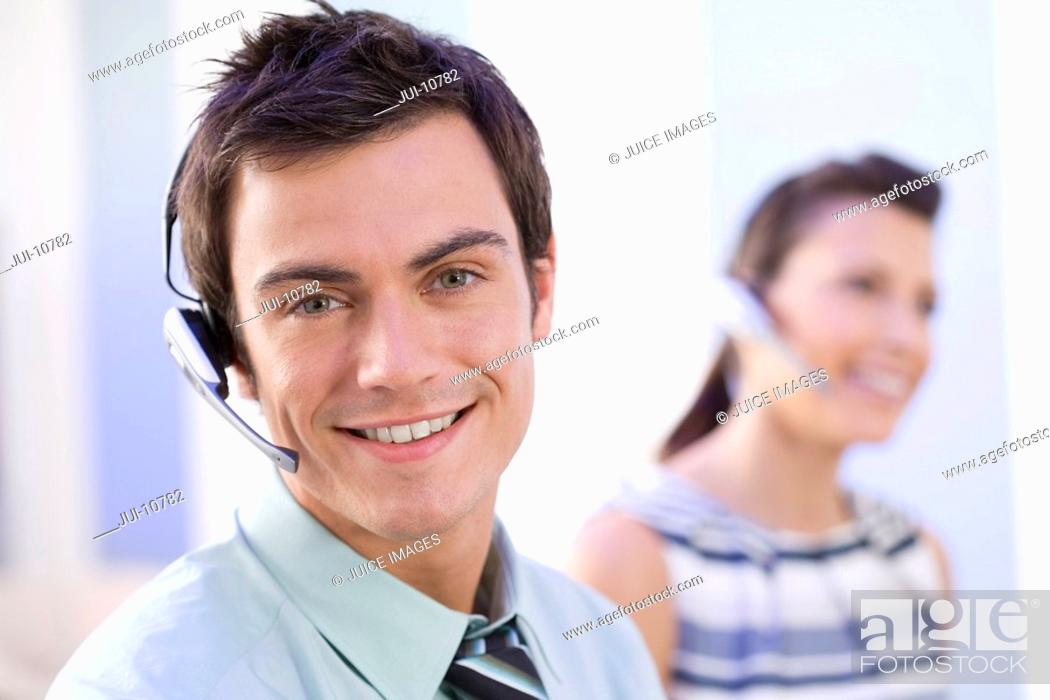 Stock Photo: Man in headset by colleague, smiling, portrait, close-up.