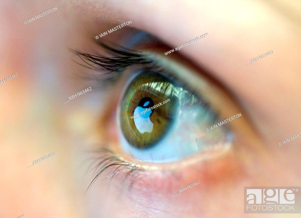 Stock Photo: Logo of Apple computer reflected from website on computer screen onto womans eye 2008.