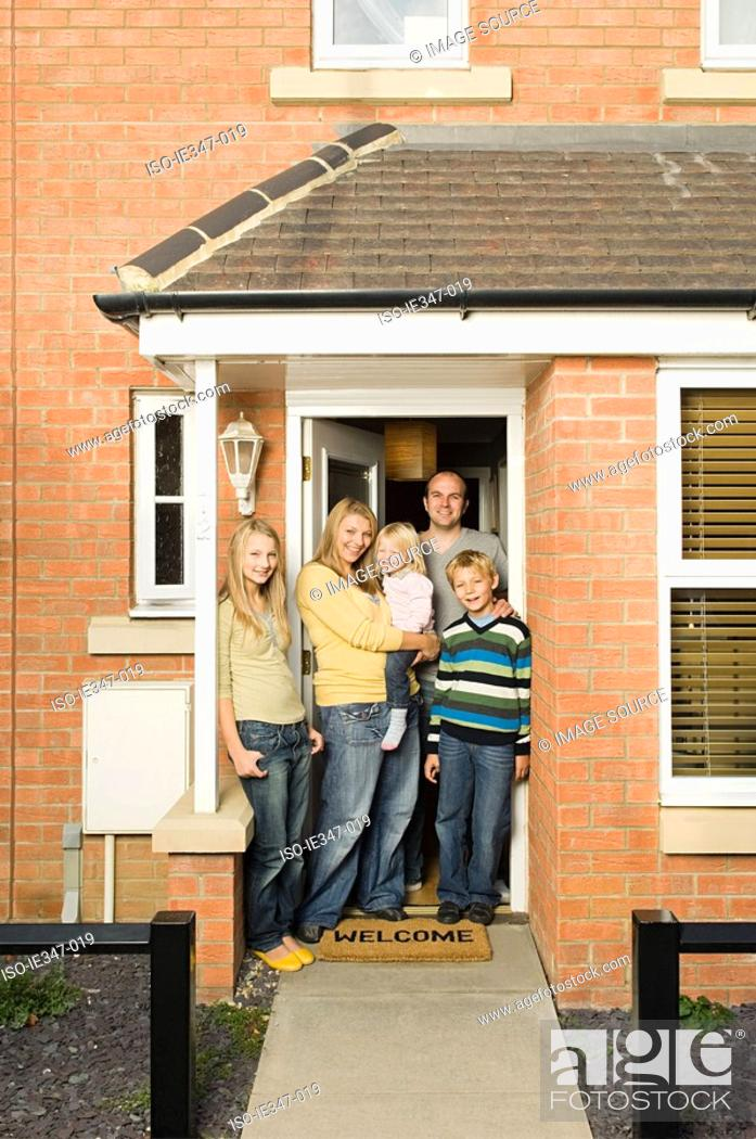 Stock Photo: Family at front door of house.