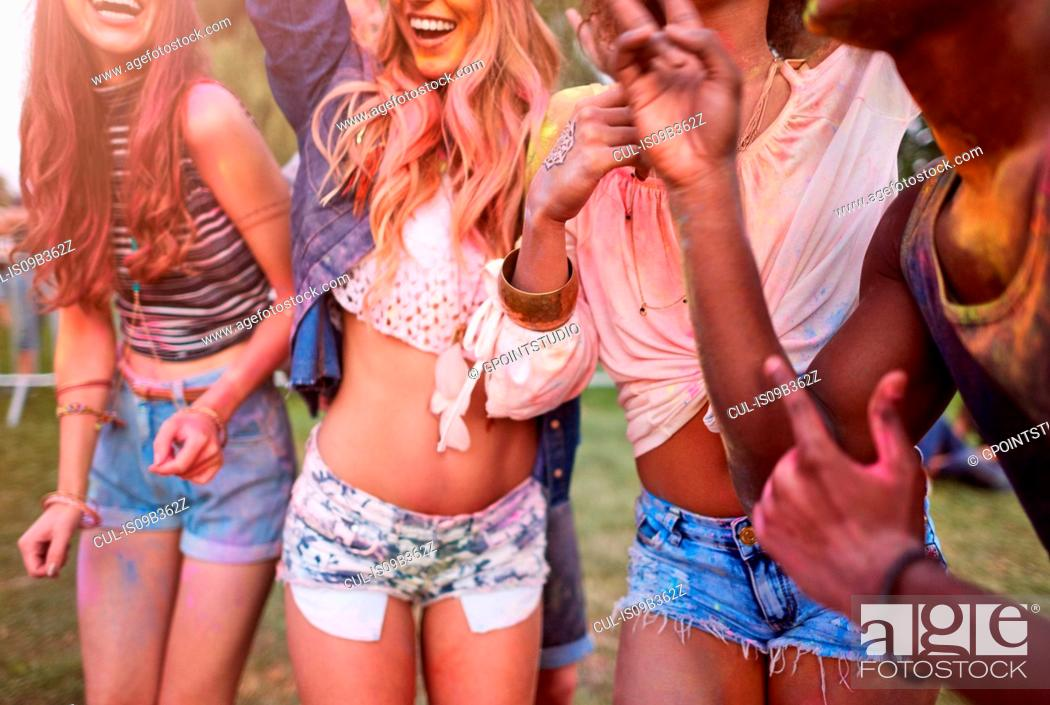 Stock Photo: Group of friends at festival, covered in colourful powder paint, mid section.
