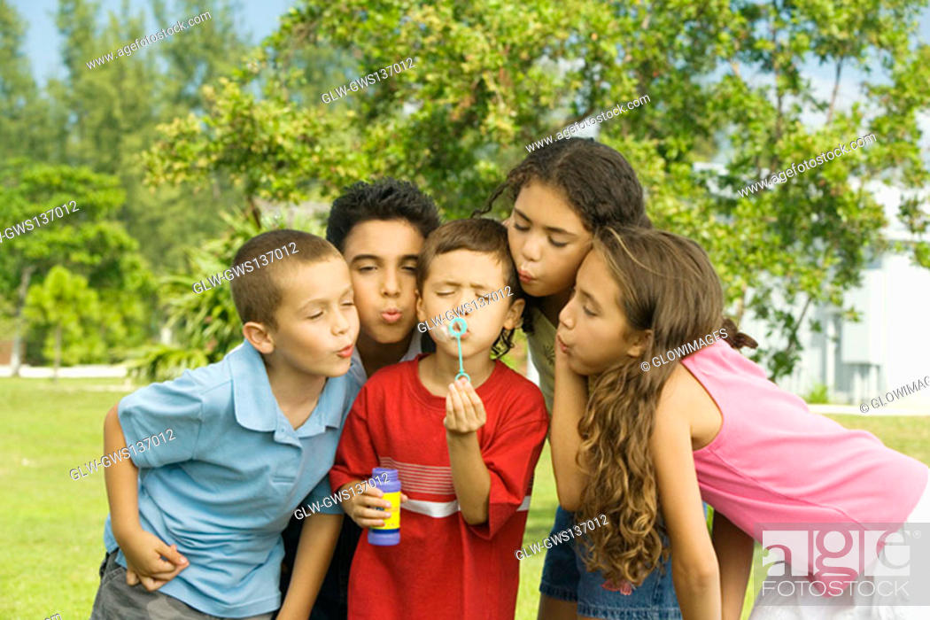 Stock Photo: Boys and girls blowing bubble wands.