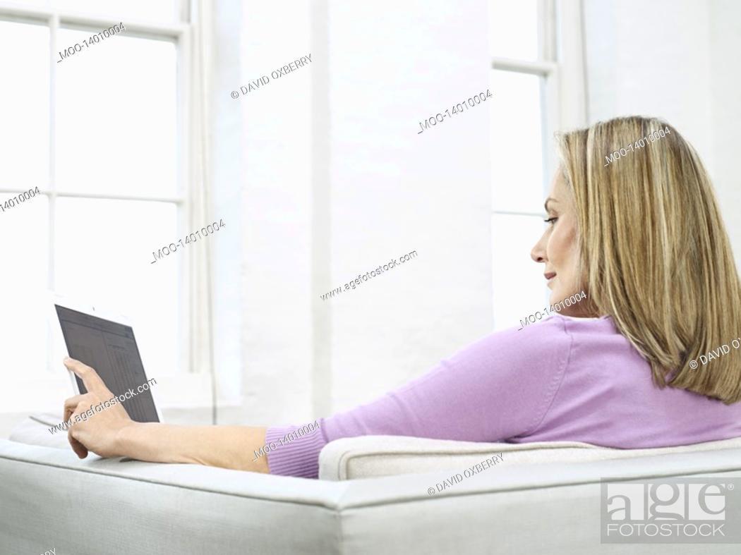 Stock Photo: Mid adult woman using laptop on sofa profile.