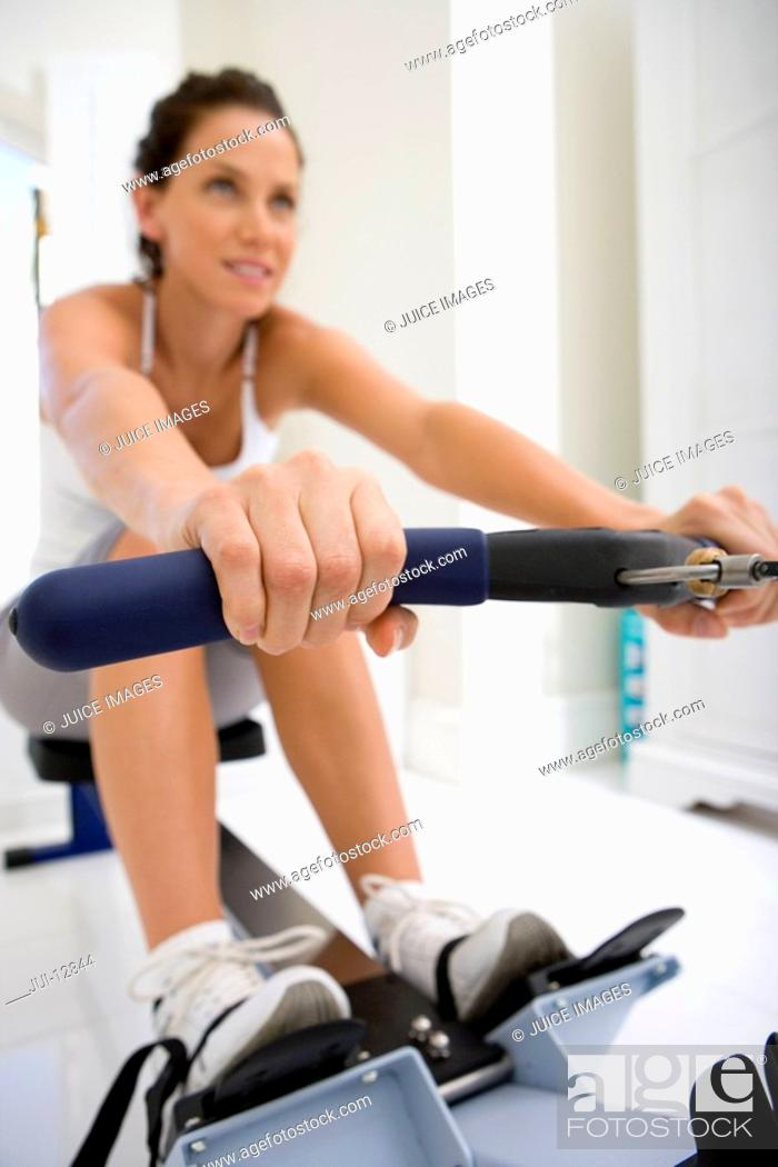 Stock Photo: Young woman on rowing machine, low angle view.