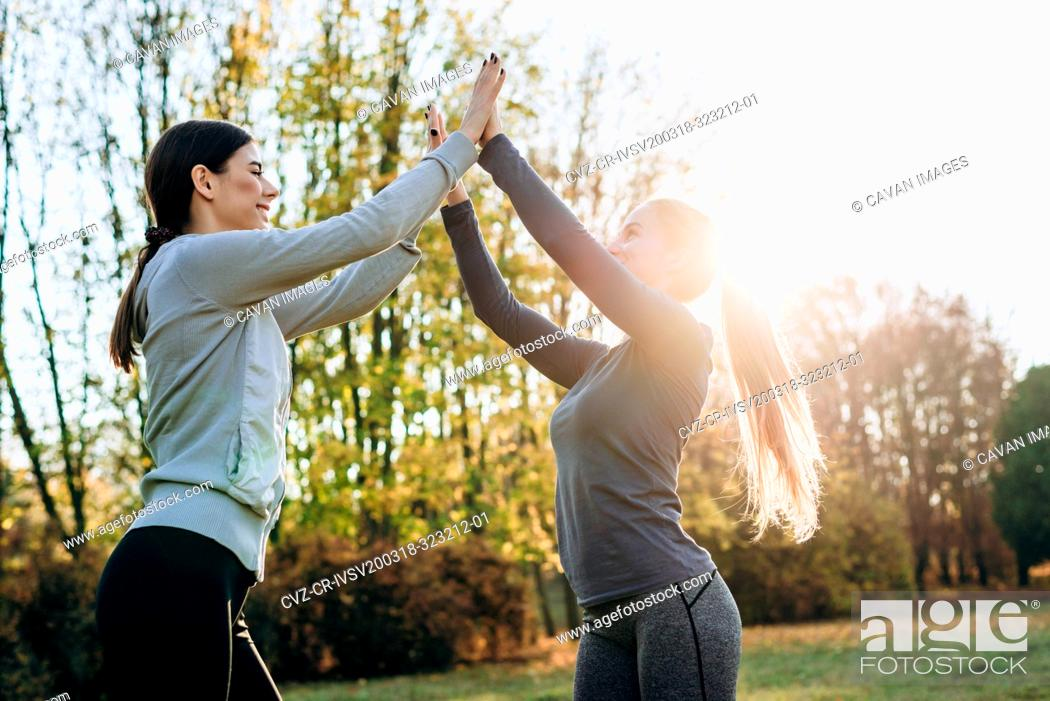 Stock Photo: Young girls raising their hands up, jointly perform gymnastic exercises, the conception of a healthy lifestyle.