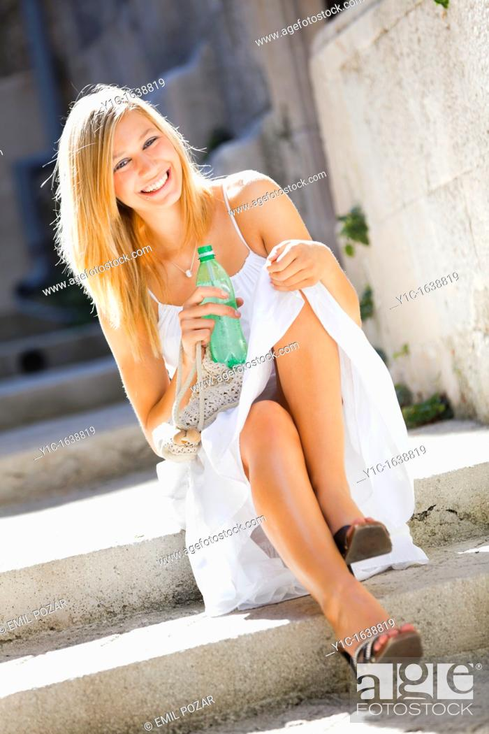 Stock Photo: Happy young woman with a bottle of drinking water in hand.