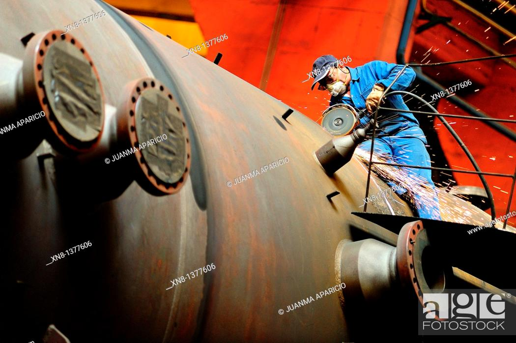 Stock Photo: Metal worker making a chamfer with the wheel for a weld on top of a piece.
