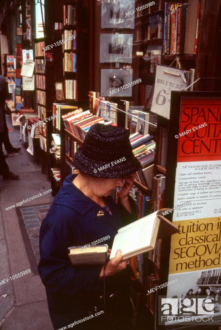 Stock Photo: London Street Scene -- a woman peruses a book on the pavement outside a book shop.