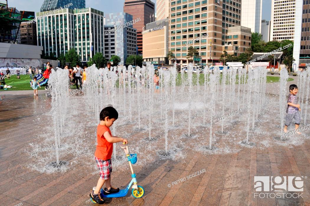 Stock Photo: Seoul (South Korea): children playing by the fountain in Seoul Square.