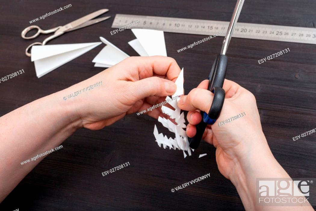 top view of hand with scissors cut a figure of snowflake