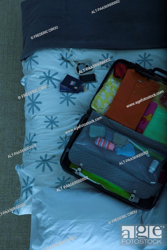 Stock Photo: Packed suitcase lying open on bed.