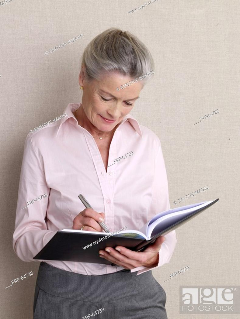 Stock Photo: Senior adult in business clothing holding datebook.