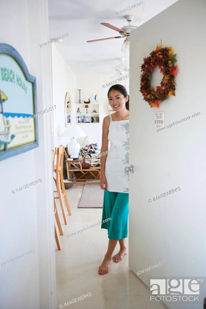 Stock Photo: A young woman standing by door.