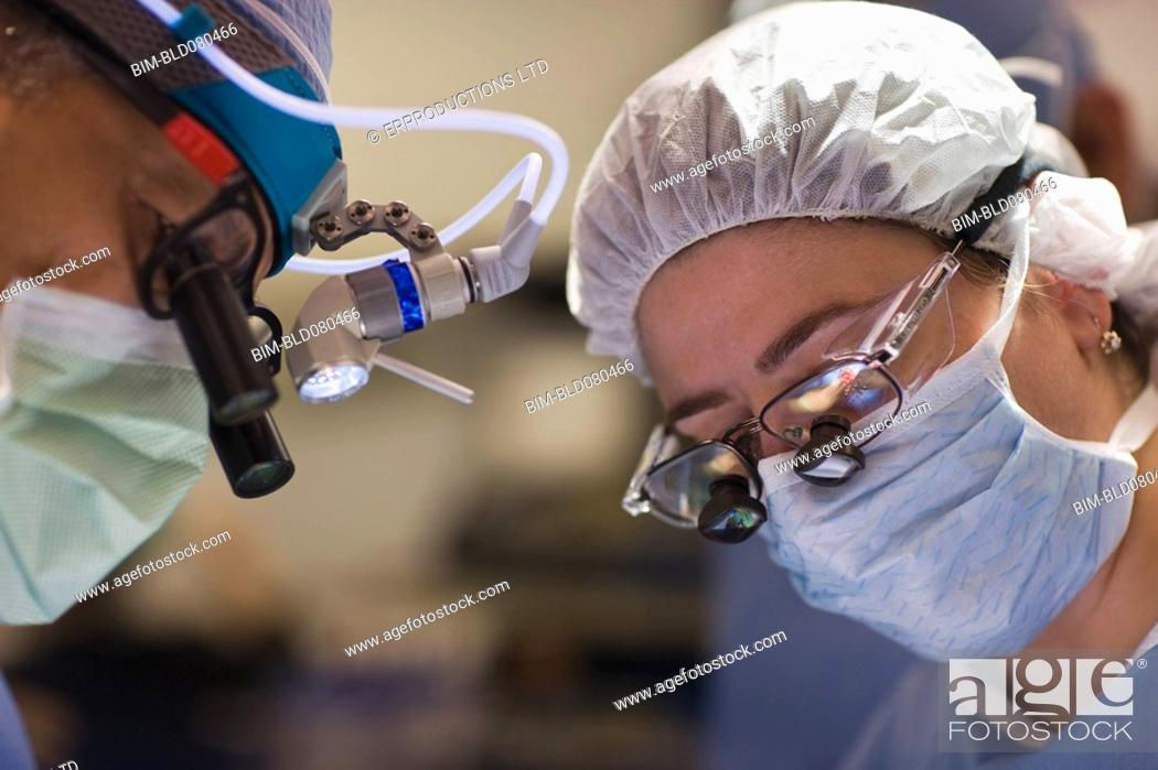 Stock Photo: Doctors performing surgery in operating room.