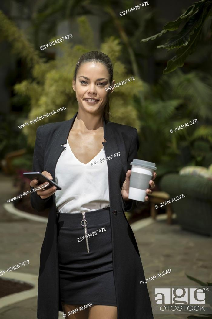 Imagen: Beautiful fit woman in elegant black suit holding coffee cup and smartphone while smiling at camera in sunlight.