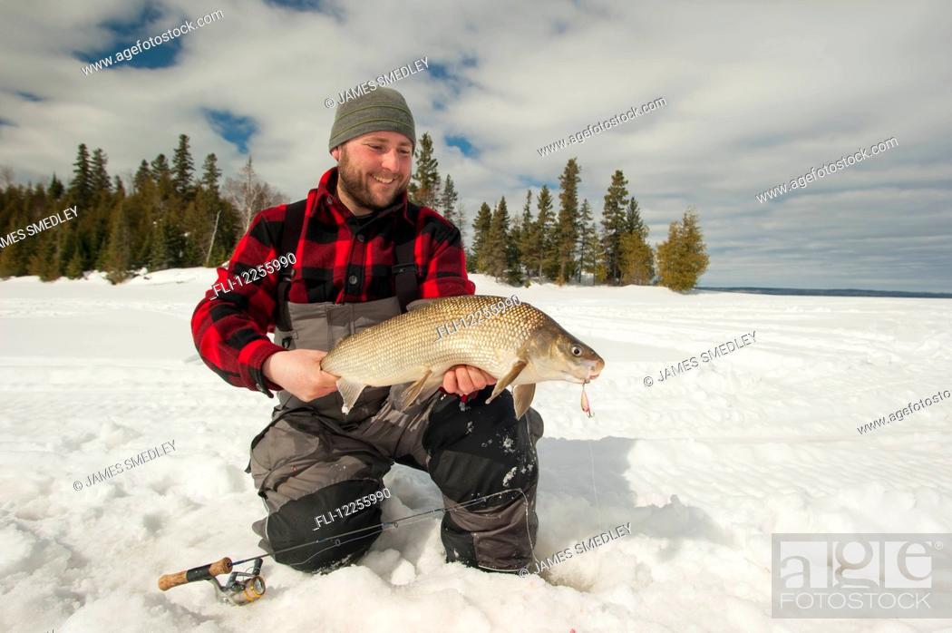 Stock Photo: Ice fisherman holding a large whitefish; Ontario, Canada.