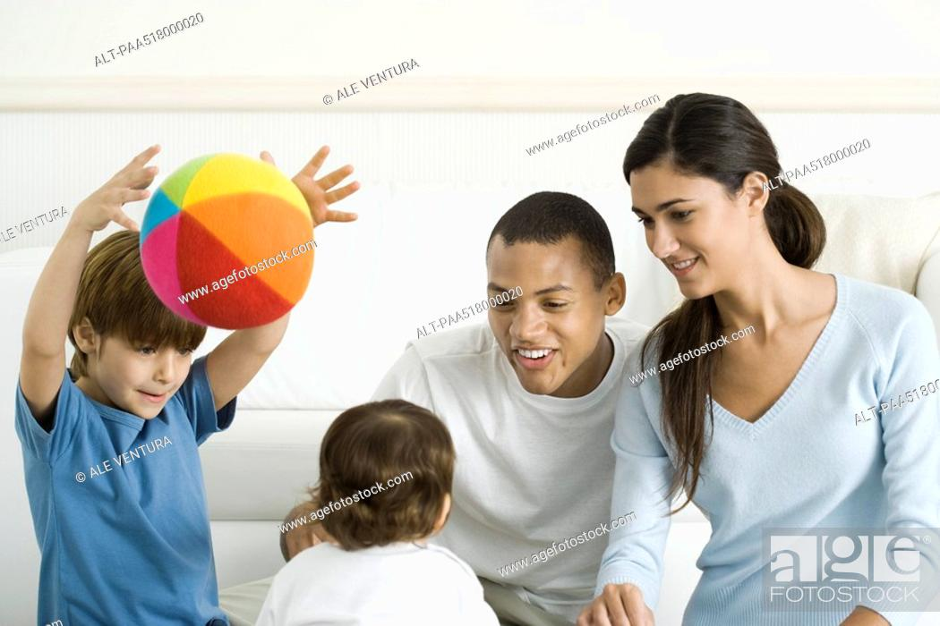 Stock Photo: Family gathered around toddler girl, smiling, boy throwing ball in the air.