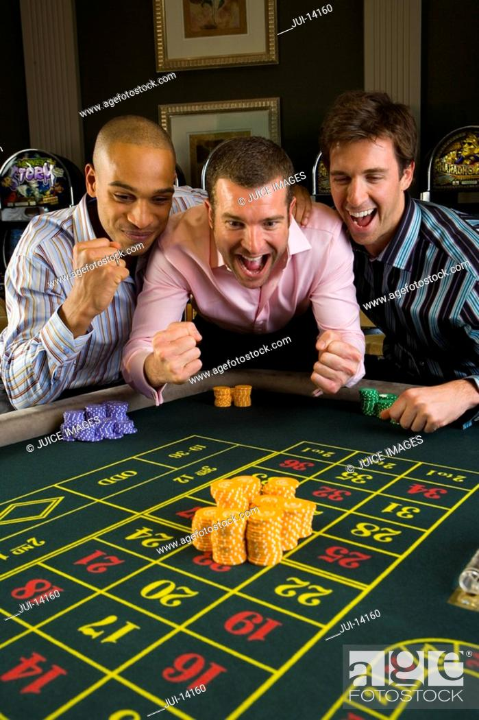 Stock Photo: Young man with friends gambling at roulette table in casino, smiling.