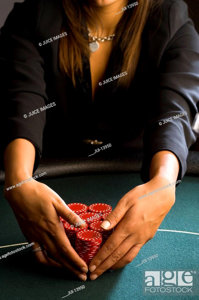 Stock Photo: Woman collecting piles of gambling chips on table, mid section.