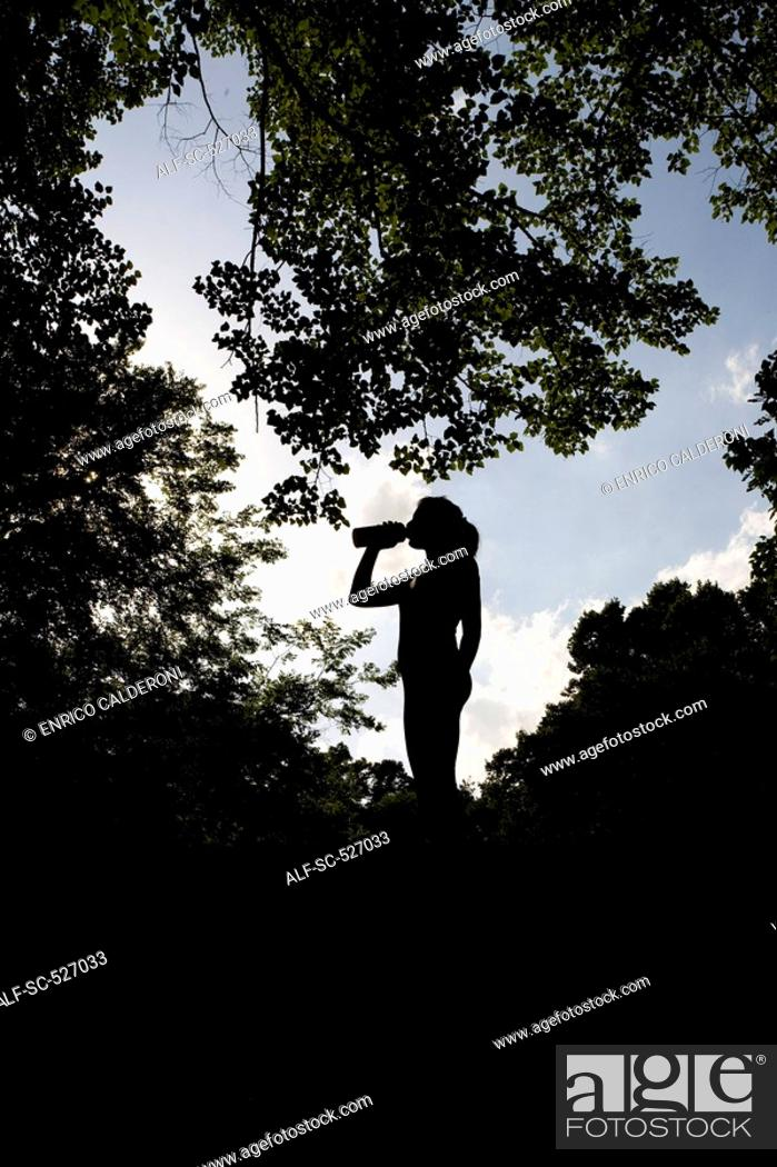 Stock Photo: Silhouette of a Jogger relaxing and drinking water.