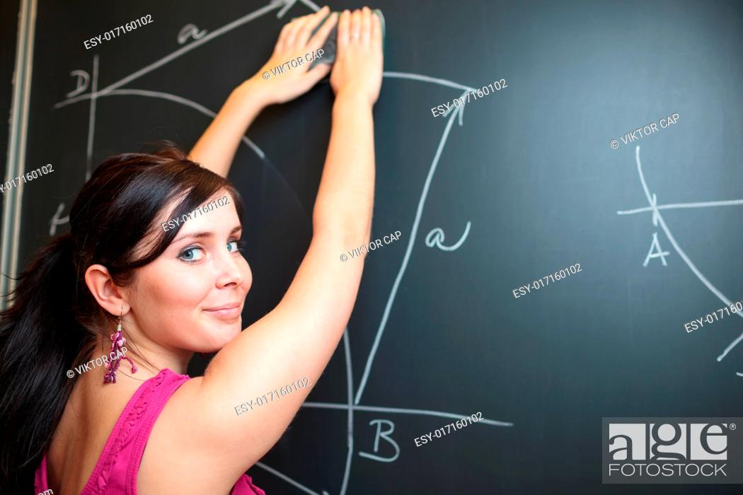 Stock Photo: Pretty, young college student drawing on the chalkboard/blackboard during a math class (shallow DOF color toned image).