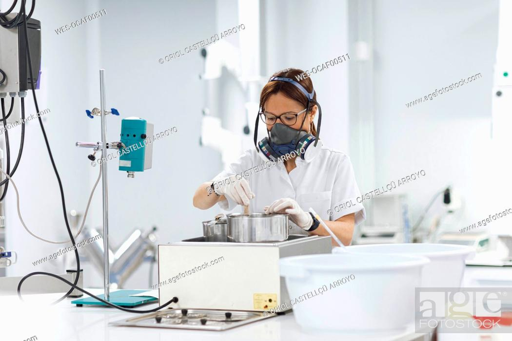 Stock Photo: Confident mature female technician doing research in lab.