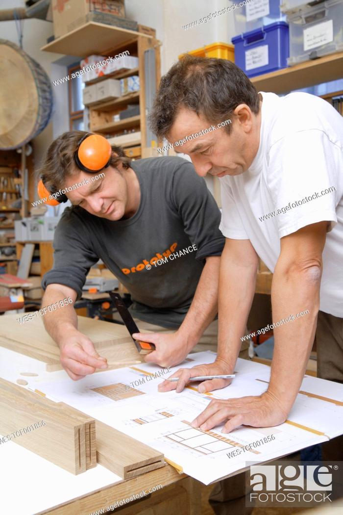 Stock Photo: Germany, Upper Bavaria, Schaeftlarn, Carpenters preparing blue print.
