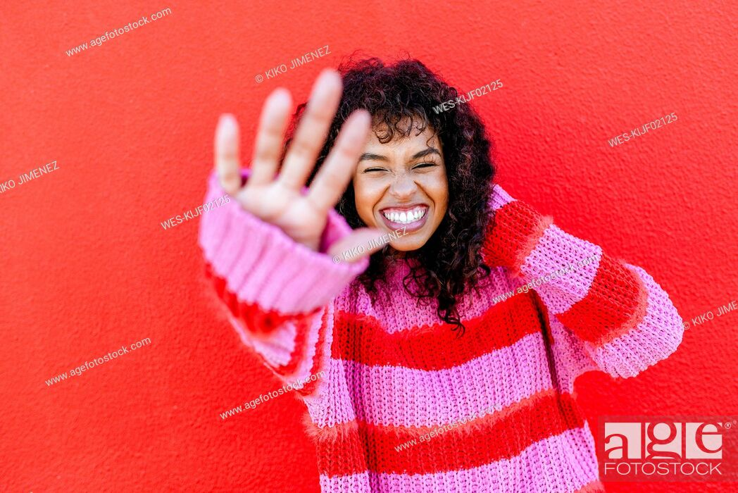 Stock Photo: Portrait of laughing young woman in front of red wall.