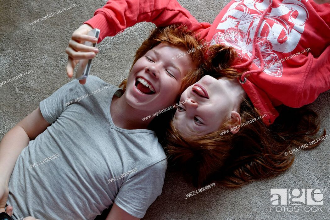 Stock Photo: Portrait of brother and sister lying on the floor taking selfies with smartphone.