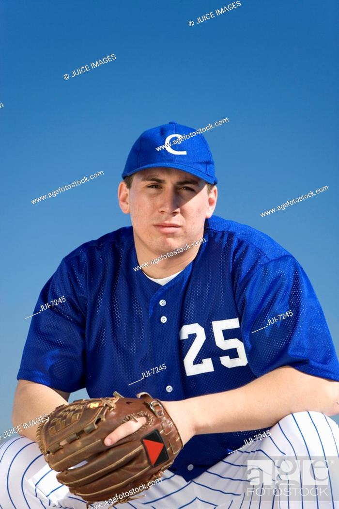 Stock Photo: Baseball player wearing blue uniform, protective glove and cap, crouching on pitch, front view, portrait.