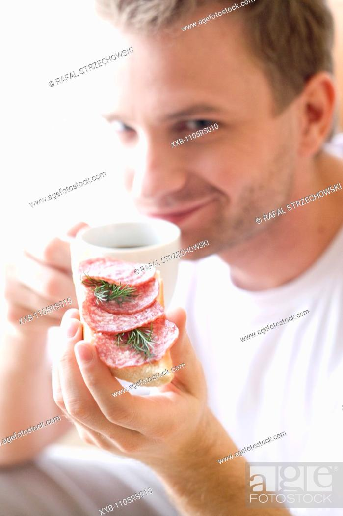 Stock Photo: man with salami sandwich and cup of coffee.
