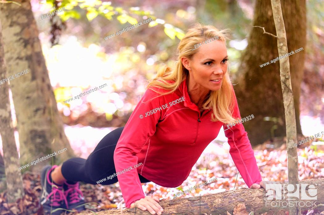 Stock Photo: A 38 year old blond woman wearing work-out clothing doing a push-up on a log in a forest setting in the fall.