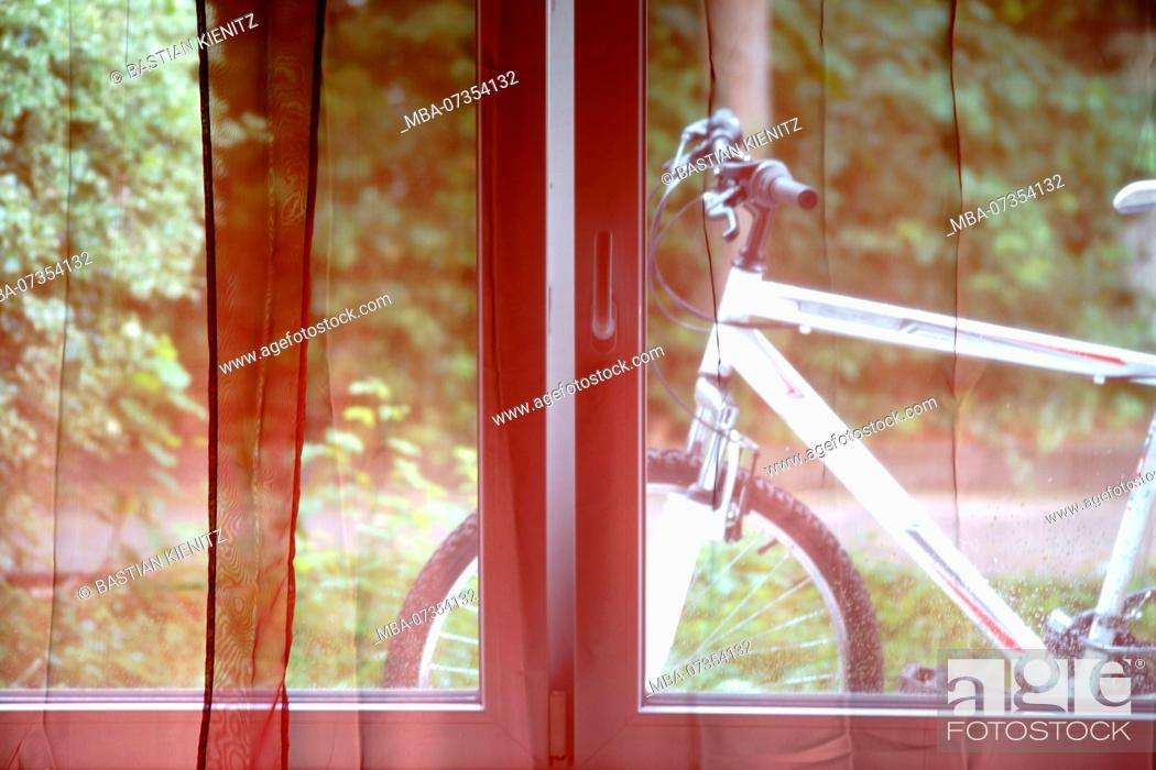 Stock Photo: A mountain bike behind the curtains of a window,.