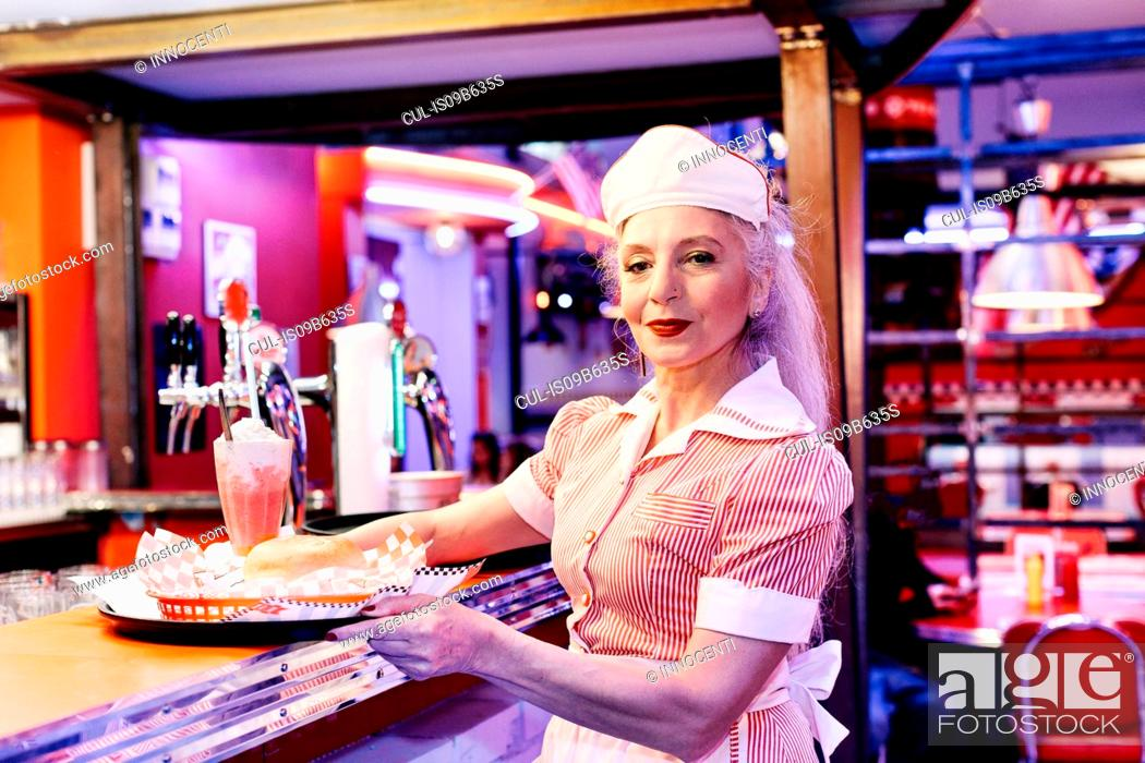 Stock Photo: Portrait of mature female waitress in 1950's diner.