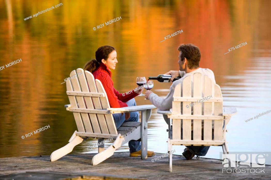 Stock Photo: caucasians, age 30's to 40's, lake, dock, wine, adirondack chairs, autumn, reflection.