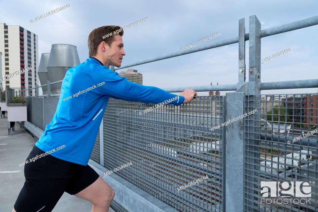Stock Photo: Man stretching on parking lot at the fence.