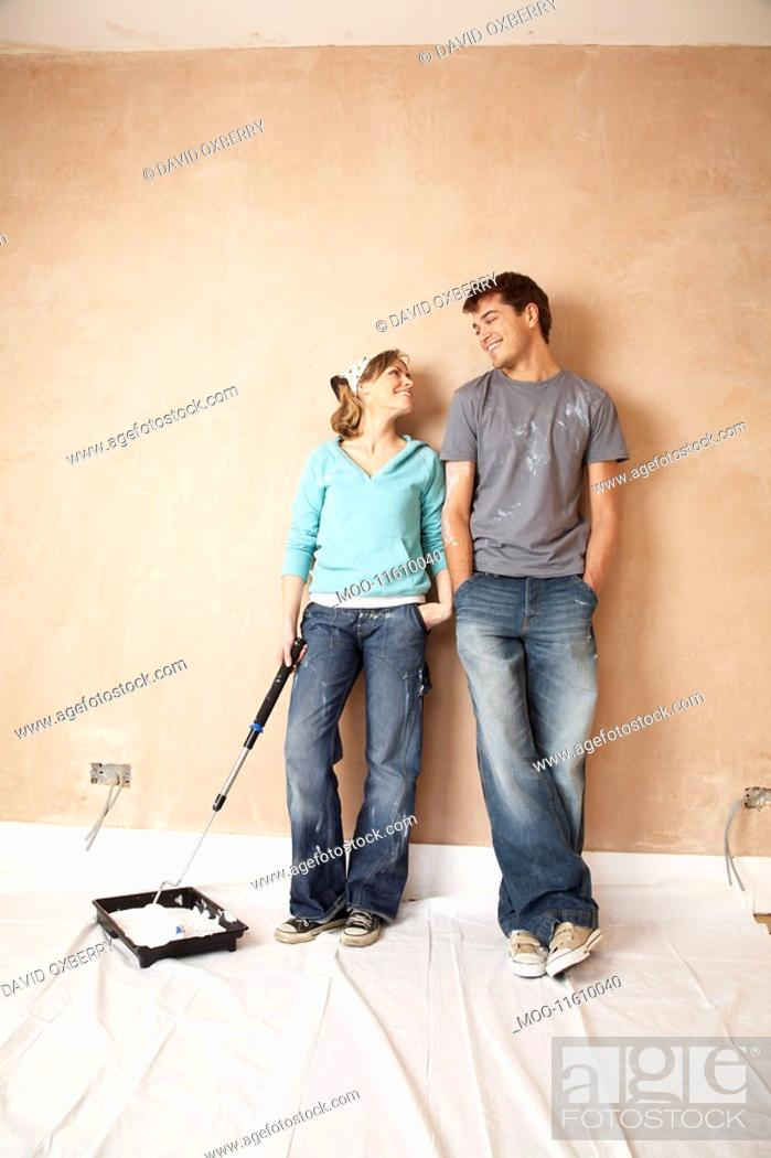 Stock Photo: Couple standing with paint roller in unrenovated room.