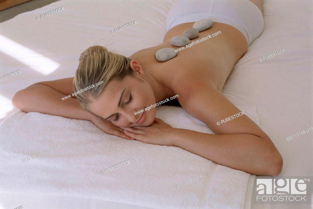 Stock Photo: High angle view of a young woman with therapeutic stones on her back.