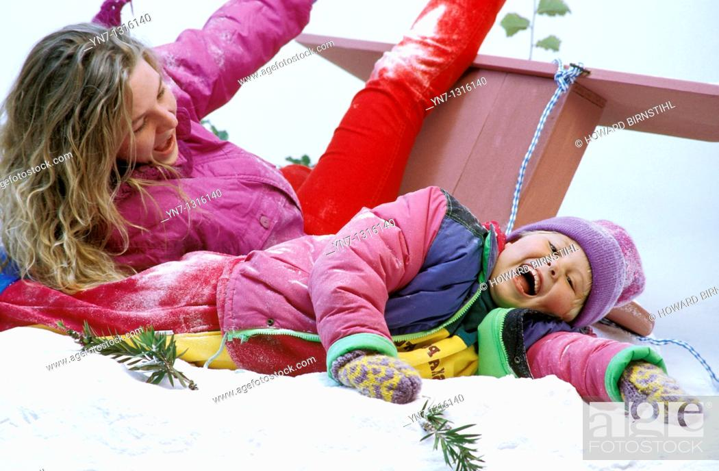 Stock Photo: mother and daughter enjoying crashing their sled in the snow.
