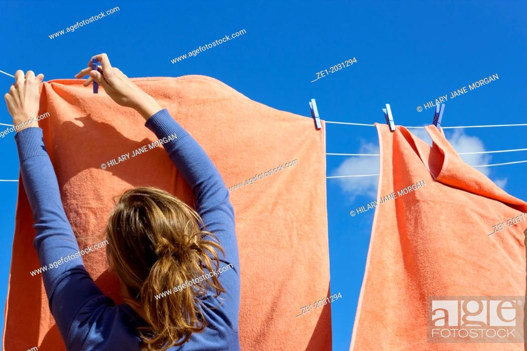 Stock Photo: Young woman pegging out washing to dry.